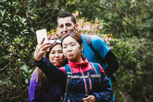 Happy friends taking selfie while standing in forest - CAVF49989
