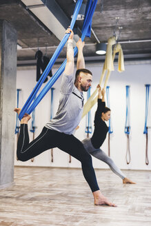 Friends stretching using hammocks while practicing aerial yoga in gym - CAVF50001