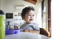 Close-up of cute cheerful baby boy holding breads while looking away at home - CAVF50013