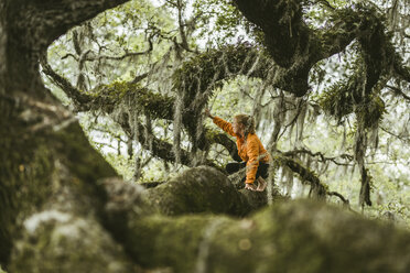 Young woman crouching on mossy branch at rainforest - CAVF50040
