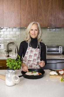 Portrait of confident senior woman preparing pizza in kitchen at home - CAVF50082
