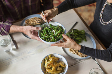 Midsection of man giving bowl of cooked green beans to woman at dining table - CAVF50085