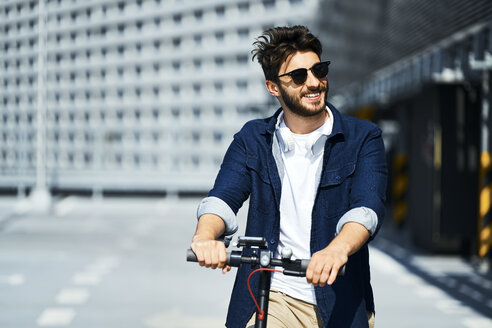 Portrait of smiling man with electric scooter outdoors - BSZF00760