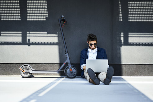 Relaxed young man sitting on the ground besides his electric scooter using laptop - BSZF00769