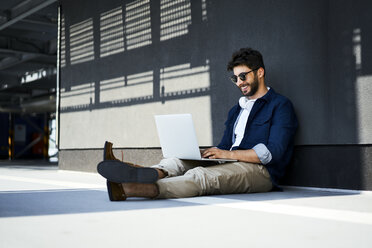 Relaxed young man sitting on the ground using laptop - BSZF00772