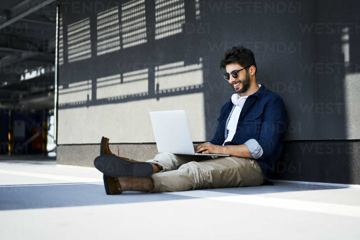 Relaxed young man sitting on the ground using laptop - BSZF00772 - Bartek Szewczyk/Westend61
