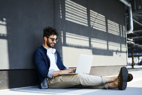 Smiling young man sitting on the ground using laptop - BSZF00775