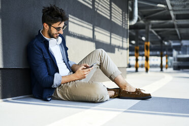 Smiling young man sitting on the ground using smartphone - BSZF00778