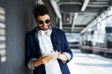 Smiling young man leaning against wall using digital tablet - BSZF00781