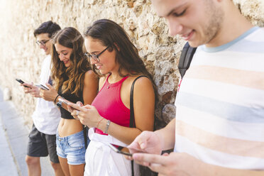 Group of friends standing at a wall using their cell phones - WPEF00921
