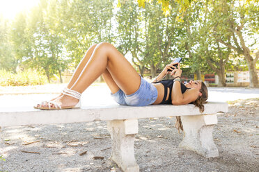 Young woman relaxing on a bench at park using cell phone - WPEF00930