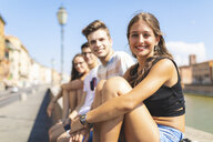 Italy, Pisa, group of four happy friends sitting on a wall along Arno river - WPEF00939