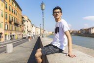 Italy, Pisa, young man sitting on a wall along Arno river - WPEF00945