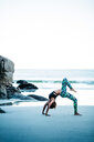 Young woman practicing yoga on the beach against a clear sky - INGF02638