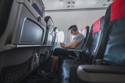 Man in airplane, using smartphone, headphones - KKAF02453