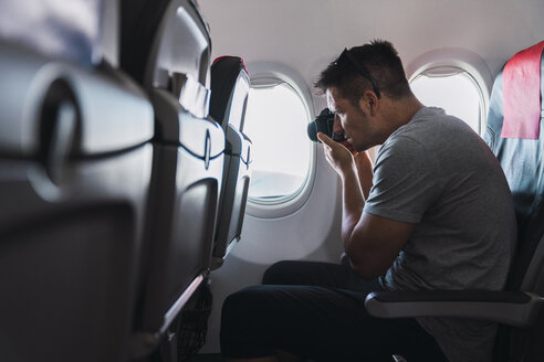 Man taking a picture in airplane - KKAF02465