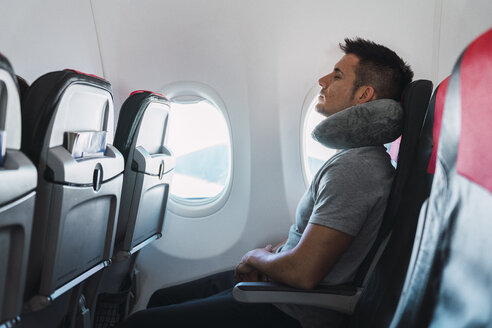 Man sleeping with neck pillow in airplane - KKAF02468