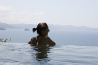 Rear view of woman swimming in infinity pool against sky - CAVF50102