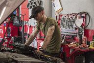 Mechanic repairing car in auto repair shop - CAVF50111