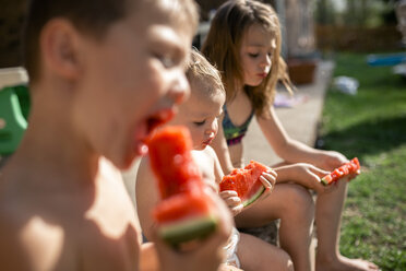 Siblings eating watermelons while sitting at yard - CAVF50120