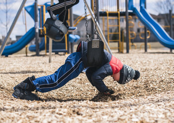 Side view of boy swinging at playground - CAVF50123