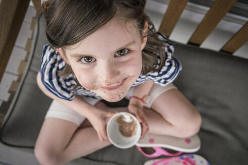 High angle portrait of cute girl with messy mouth eating chocolate while sitting on chair at home - CAVF50162