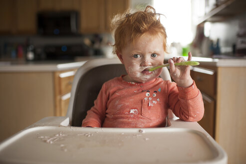 Portrait of cute baby boy with messy face eating food while sitting on high chair at home - CAVF50177