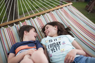 High angle view of happy siblings talking while relaxing on hammock at yard - CAVF50180