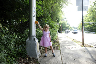 Cute girl looking away while pushing crosswalk button on road - CAVF50198