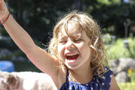 Close-up of happy girl with hand raised screaming while standing in yard - CAVF50201