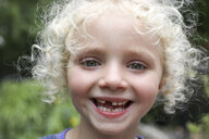 Close-up portrait of happy girl with messy blond hair standing at yard - CAVF50204
