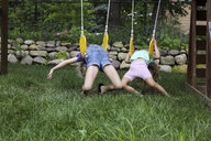 Happy playful sisters lying on swings at playground - CAVF50207