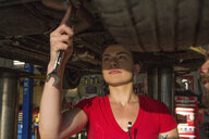 Female mechanic examining vehicle parts while standing below car in auto repair shop - CAVF50237