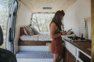 Side view of woman using mobile phone while standing by kitchen counter in motor home - CAVF50255