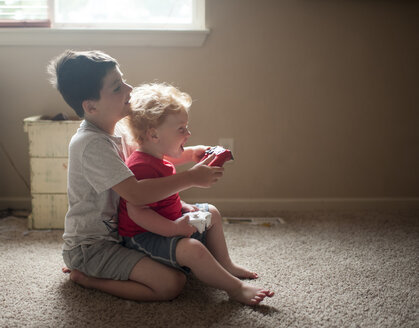 Side view of brothers playing video game while sitting on rug at home - CAVF50267