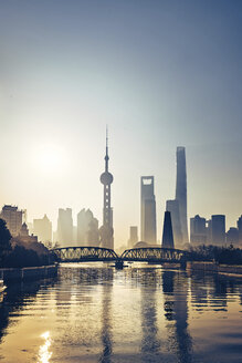 Silhouette bridge over Huangpu River against modern skyscrapers during sunset - CAVF50270