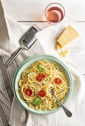 High angle view of spaghetti served in plate with drink and cheese on table - CAVF50303