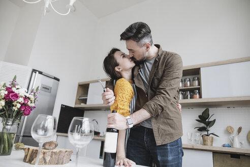 Couple in love kissing in the kitchen - KMKF00575