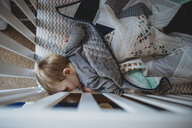 High angle view of baby boy sleeping in crib at home - CAVF50308