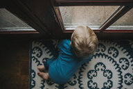 High angle view of baby boy looking through wet window at home - CAVF50311