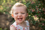 Close-up of happy baby girl standing against plants at park - CAVF50323