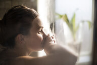 Close-up of pregnant woman in labor at home by window - CAVF50362