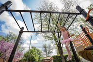 Low angle view of girl in ballet costume hanging on monkey bars against cloudy sky at playground - CAVF50386