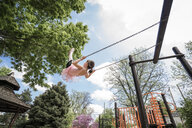 Low angle view of girl in ballet costume swinging against cloudy sky at playground - CAVF50389