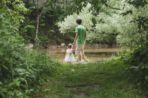 Rear view of father with daughter standing on grassy field by river at park - CAVF50407