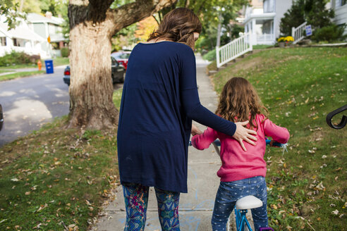 Rear view of mother assisting daughter in riding bicycle on footpath during autumn - CAVF50419