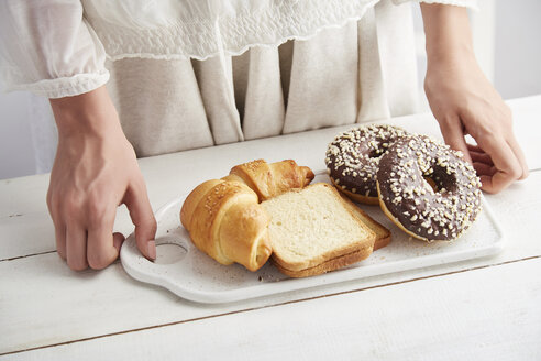 Midsection of woman holding donuts with bread and croissants in tray on table at home - CAVF50458