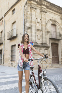 Spain, Ubeda, portrait of smiling young woman with bicycle crossing the street - JASF01967