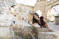 Spain, Baeza, portrait of laughing young woman splashing with water of a fountain - JASF01970