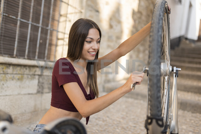 Spain, Baeza, portrait of smiling young woman repairing her bicycle with wrench - JASF01973